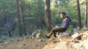 Man work with laptop sitting back to tree in nature park. Forest stock footage