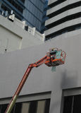 Man at Work - Painting. Singapore - July 2016 A man in a crane basket painting the outer wall of a building in the Singapore Central Business District stock images