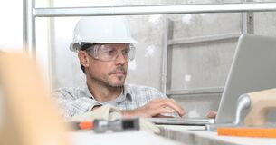 Free Man Work, Professional Construction Worker  With Computer, Plastering Tools On Scaffolding, Safety Hard Hat, Gloves And Protective Stock Photo - 174044560