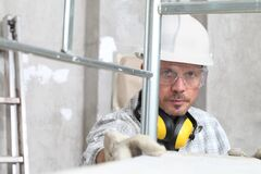 Free Man Work, Professional Construction Worker  With Scaffolding, Safety Hard Hat, Hearing Protection Headphones, Gloves And Stock Images - 174044234