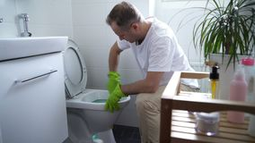 Man with a rubber glove cleans a toilet bowl. The man at work. Man with a rubber glove cleans a toilet bowl using means for cleaning stock video footage