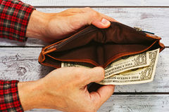 Man in work shirt holding wallet with just two dollars. Man in checkered work shirt holding old leather wallet with just two US dollars - paying debt or poverty Royalty Free Stock Photo