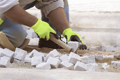 Man at work, street worker, paving. Man kneeling at work, street worker, paving with hammer in yellow gloves Stock Photography