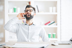 Man at work talking on phone. Cheerful caucasian man sitting at workplace and talking on cellular phone Stock Photo