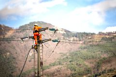 Man at work. Technician are repairing high voltage transmission systems on the power poles. stock image