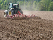 Man work with tractor and harrow. On the agriculture field in early springtime Stock Image
