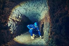 Man work underground in dark tunnel. Staff  in a protective suit check sediments. In rocky wall, large underground tunnel sewer Royalty Free Stock Photography