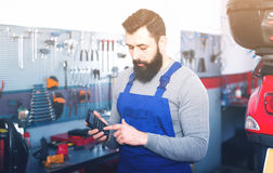 Man worker calculating sum for his service in motorcycle. Smiling man worker calculating sum for his service in motorcycle workshop Royalty Free Stock Photo