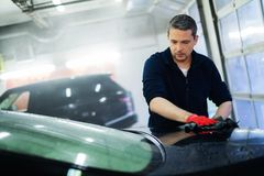 Man worker on a car wash. Cheerful worker wiping car on a car wash Stock Images