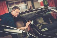 Man worker on a car wash. Man worker polishing car on a car wash Royalty Free Stock Image