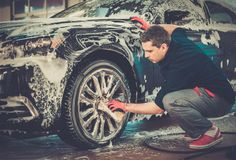 Man worker on a car wash. Man worker washing cars alloy wheels on a car wash Stock Images