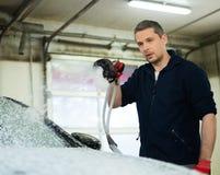 Man worker on a car wash. Man worker washing luxury car on a car wash Stock Photo