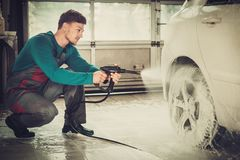 Man worker on a car wash Royalty Free Stock Image
