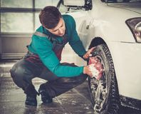 Man worker on a car wash. Man worker washing car's alloy rims on a car wash Royalty Free Stock Photo