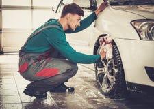 Man worker on a car wash. Man worker washing car's alloy rims on a car wash Stock Photos