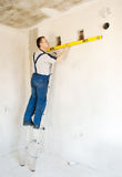 Man Worker Checks The Wall With A Level Royalty Free Stock Image