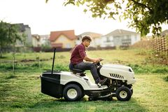 man worker cutting grass with lawn mower, lawn care concept. Industrial details royalty free stock image