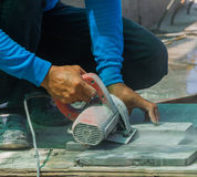 Man worker cutting tile with circular saw. Stock Photography