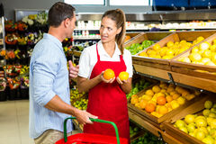 Man and worker discussing fruit. In grocery store Stock Image