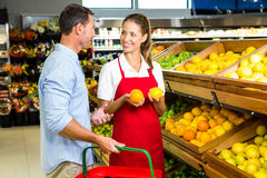 Man and worker discussing fruit. In grocery store Royalty Free Stock Photo