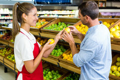 Man and worker discussing fruit. In grocery store Royalty Free Stock Photography
