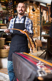 Man worker displaying various belts in leather workshop Royalty Free Stock Photography
