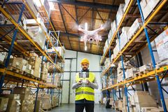 Man with drone in a warehouse. Man or a worker with drone standing in a warehouse stock photography