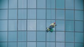 A man worker hanging on ropes by the exterior windows of a skyscraper and cleaning them - industrial alpinism