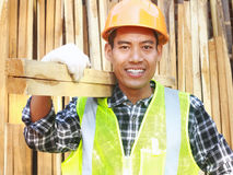 Man worker with helmet and safety vest carrying wood. Man worker carpenter with helmet and safety vest carrying wood smiling look on your camera Royalty Free Stock Images