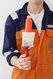 Man worker is holding paint brush and color tube Stock Photo