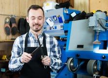 Man worker honing his tools for repairing. In shoe repair workshop stock image