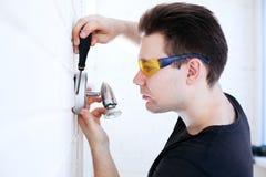 Man worker installing lamp Stock Image