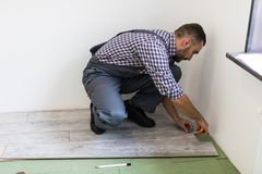 Man worker installing new wooden laminate flooring in new apparment. Man worker installing new wooden laminate flooring royalty free stock images