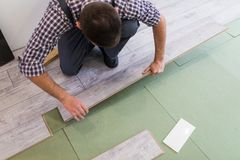 Man worker installing new wooden laminate flooring in new apparment. Man worker installing new wooden laminate flooring royalty free stock photos