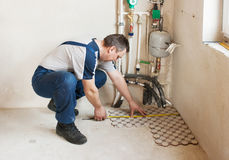 Man worker lays on the floor tiles Stock Image