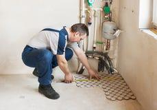 Man Worker Lays On The Floor Tiles Stock Image