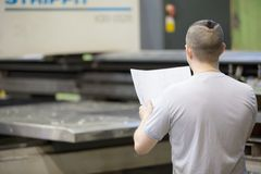 Man worker look drawing blueprints in factory workshop Royalty Free Stock Photos