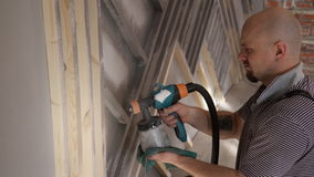 Man worker painting wood with spray gun repair in house stock video footage