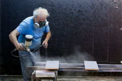 Man worker painting wooden board with spray gun Royalty Free Stock Images