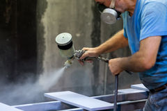 Man worker painting wooden board with spray gun Stock Photography