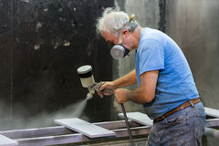 Man worker painting wooden board with spray gun Royalty Free Stock Photos