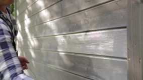 Man worker painting wooden house exterior wall with paintbrush and wood protective color stock video