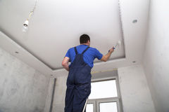 Man worker paints the ceilin inside of the room interior Royalty Free Stock Images