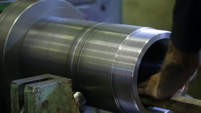 Man worker polishing metal part inside machine tool. A large metal piece rotates at high speed, it is fixed to machine spindle. A worker with bare hairy arms stock video footage