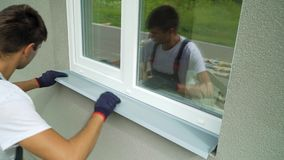 Man worker in protective gloves measuring external frame and PVC window metal sill size. Builder checking components fitting of construction outside building stock video