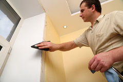 Man Worker putting up wallpaper Stock Image