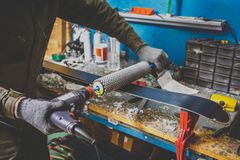 A man worker repairs in the ski service workshop the sliding surface of the skis, Base polishing, final ski polishing. In the royalty free stock photo