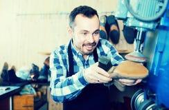 Man worker restore footwear in repair workplace. Positive man worker restore footwear in repair workplace Royalty Free Stock Image