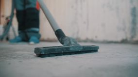 Man in worker robe blue shoes steering vacuum cleaner hose over concrete floor. Man in worker robe blue shoes steering vacuum cleaner hose black plastic nozzle stock footage
