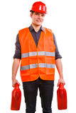 Man worker in safety vest hard hat with canisters. Young man construction worker in orange safety vest and red hard hat holding plastic canisters isolated on Royalty Free Stock Photo